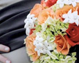 Her maid of honor carried green hydrangea, two shades of orange roses and accents of stephanotis. The bouquet was finished in brown ribbon to match the sash on her gown.