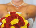 The bridal bouquet, full of red and yellow roses and accents of golden yarrow.