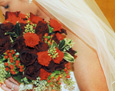 For her Christmas wedding, the bride carried Black Magic roses, red mini carnations, red hypericum berries, naked seeded eucalyptus, and variegated holly.