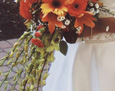 This cascading bouquet included dendrobium orchid sprays, orange lilies, orange mini-gerbera, full-sized light orange gerbera, red carnations, and white Monte Cassino aster sprays.