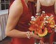 Her attendants carried matching hand-tied bouquets with orange lilies, yellow gerbera, dark orange mini-gerbera, red mini carnations, and white Monte Cassino spray aster.