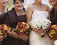 Her bridesmaids carried yellow gerbera, orange mini gerbera, orange roses, Black Magic roses, Leonida roses, dark red hypericum berries, and accented with silk fall leaves and acorns.