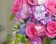 A bouquet with blue hydrangea, light pink mini gerbera, hot pink roses, lavender stock, lavender freesia, and bluporium.