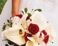 The bride carried a hand-tied bouquet of white calla lilies, white stargazer lilies, Latin Lady roses, with coffee foliage. The stems are wrapped half of the way down and a white satin bow finishes the bouquet.