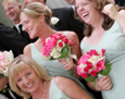 The bride carried white mini callas, white hydrangea, pale pink roses, and pink spray roses. Her attendants carried hot pink spray roses, bright pink roses, and light pink hydrangea.