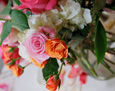 White hydrangea, hot pink roses, pale pink roses, and orange spray roses.