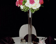 Eiffel Tower vases filled with white hydrangea, hot pink carnations and roses, and touches of variegated pittasporum and salal leaves.