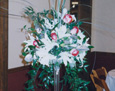 Eiffel Tower vases consisting of white stargazer lilies, Latin Lady roses, touches of silver salal leaves, and various greens to complete the look.