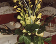This centerpiece has a tropical feel with slices of lemons and limes added to the vase, then filled with green dendrobium orchid sprays, bear grass, salal, and galax leaves.
