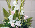 An arrangement of white glads, pale pink roses, white stock, white monte casino aster, sorbonne lily, and fern.
