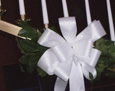 The church's candelabra is adorned with a greenery arrangement and ivory satin bow.