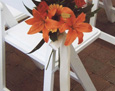 Chair decorations to match the theme of the wedding with orange Asiatic lilies, gerbera daisy, red mini carnations, and salal leaves tied with a simple ivory satin bow.