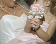 To match her dress, the flower girl carries a small nosegay of pale pink spray.