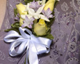 Pin on corsage with pale yellow roses, stephanotis, and lavender hyacinth blossoms.